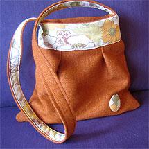 Väska sydd av ett begagnat ylletyg och ett örngott. Från ena sidan.